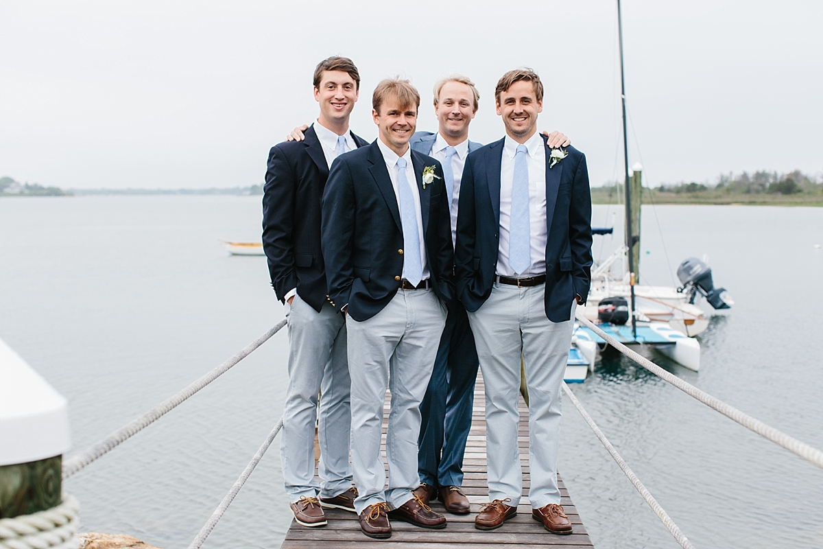 groomsmen in navy blazers and boat shoes on dock at weekapaug inn