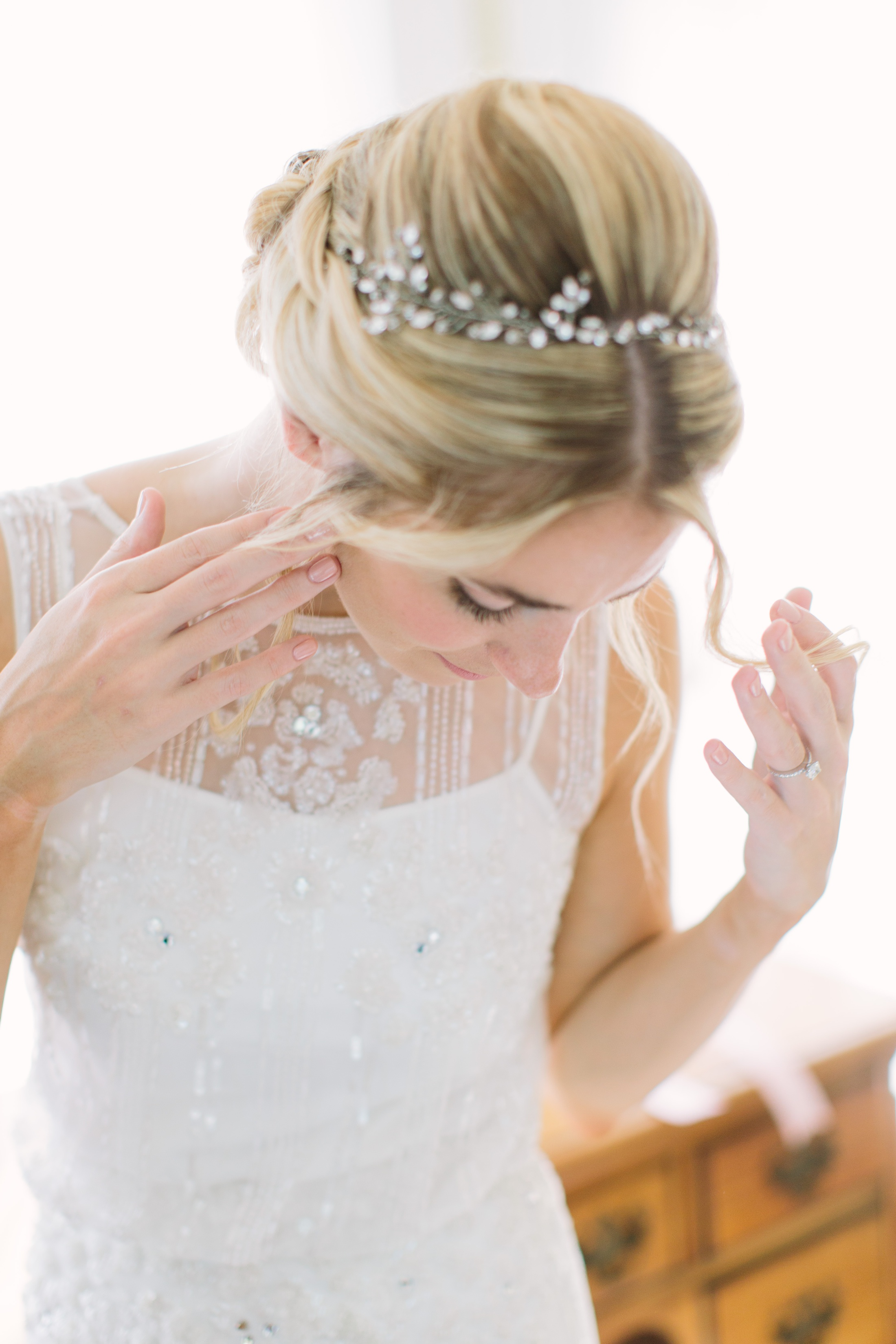 bride with sparkling dress fixing hair