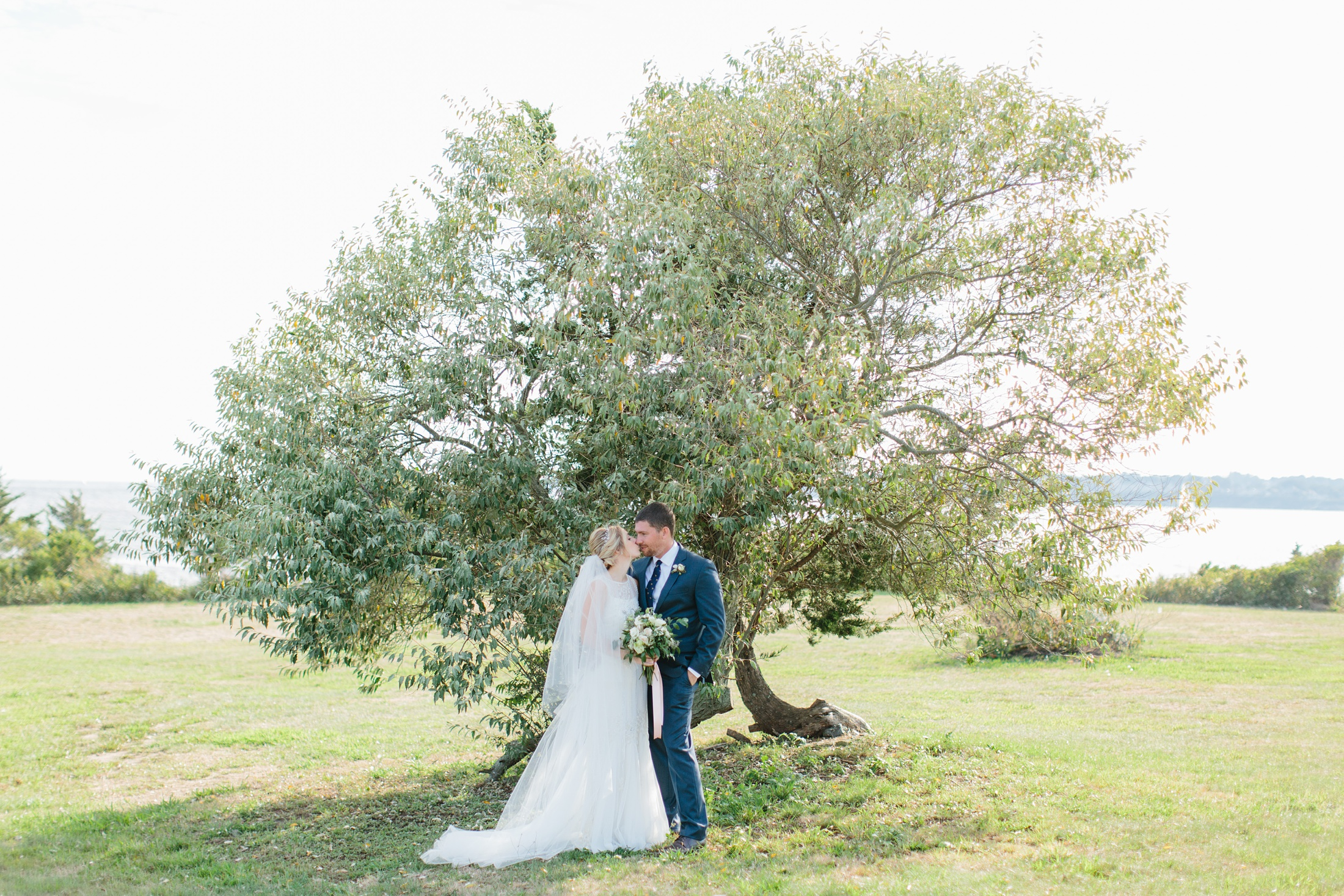 bride and groom with apple tree at fort Adams
