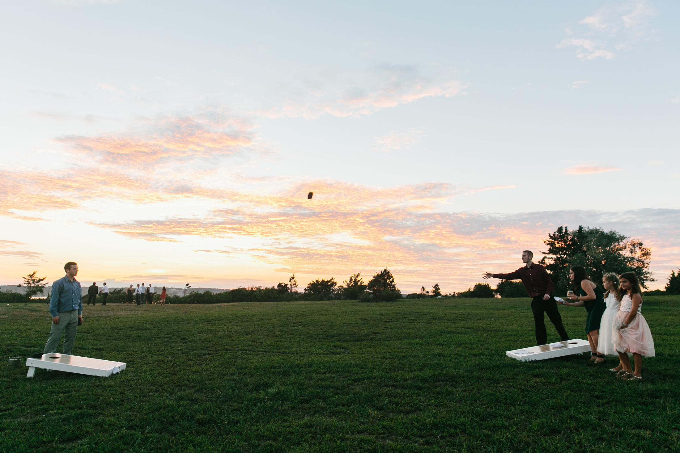 guests play corn hole at sunset at wedding