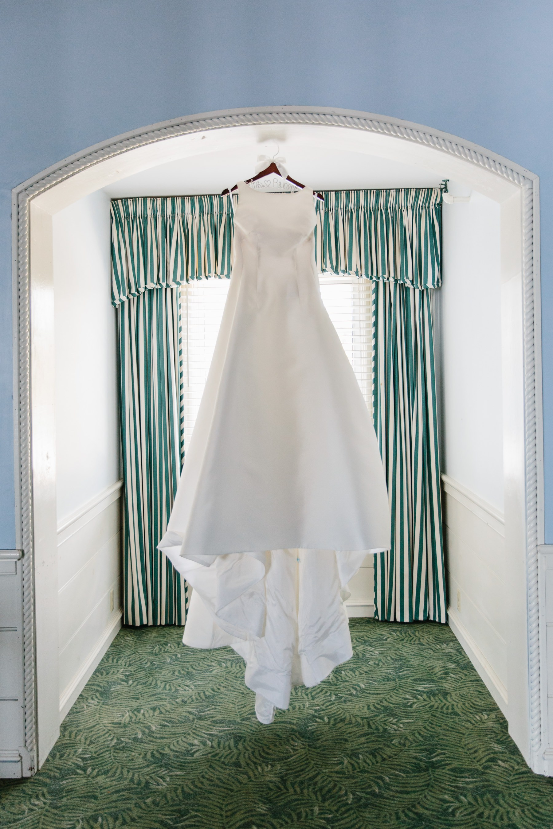 wedding dress hung at dunes club with signature stripes